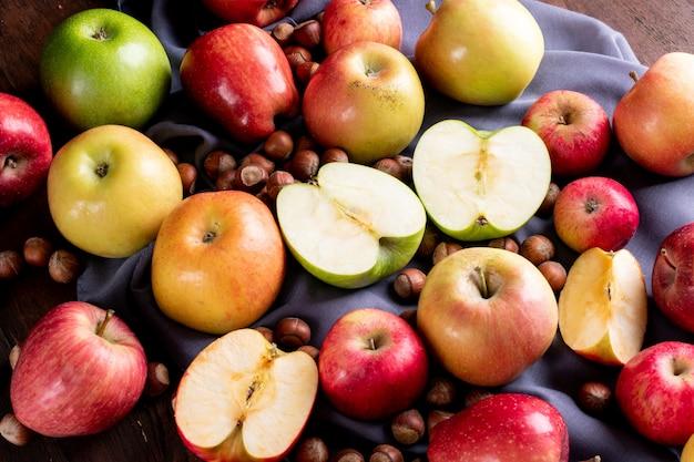 Вид сбоку яблоки с орехами на серой ткани горизонтальной