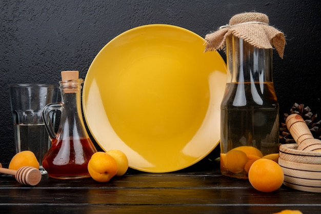 Side view of apricot compote and peach syrup with apricots and garlic crusher on wooden surface and black background
