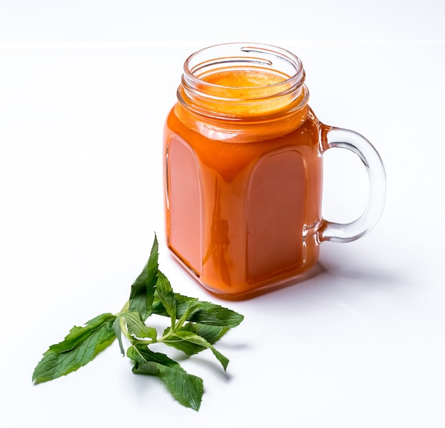 Side view of apricot smoothie in a glass jar with handle and mint on white surface