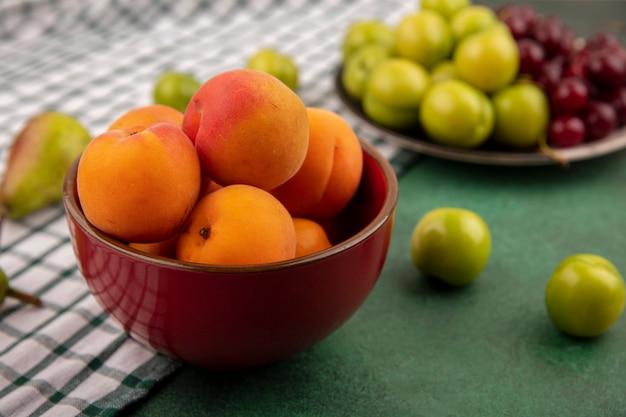 Vista laterale di albicocche nella ciotola e prugne ciliegie nel piatto con pera su un panno plaid e sfondo verde