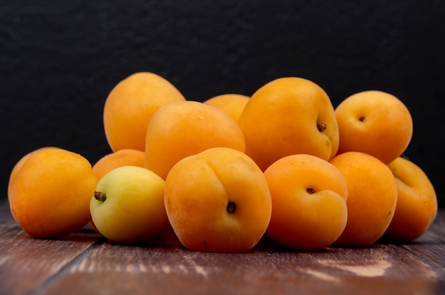 Side view of apricots on wooden surface and black background