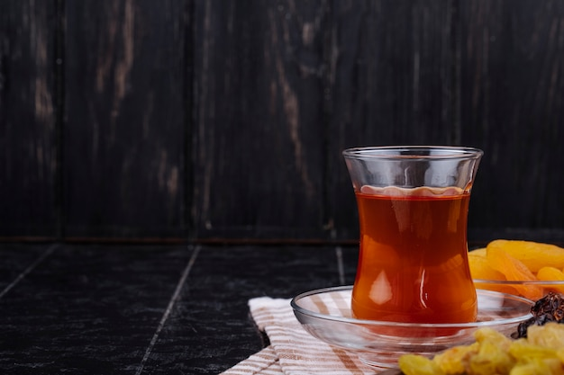 Side view of armudu glass of tea with dried fruits on black rustic background