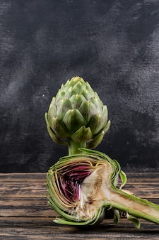 Side view artichoke and a slice on dark wooden and black background. horizontal space for text