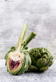 Side view artichoke and slice on light gray background. vertical space for text