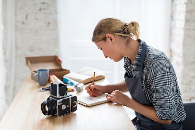 Side view of artist in apron working on desk