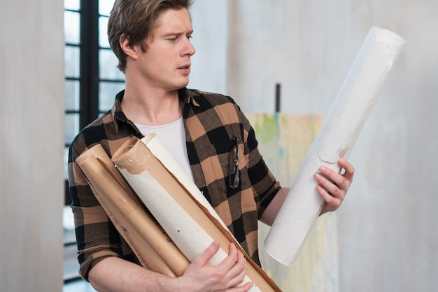 Vista laterale uomo artistico che tiene i suoi dipinti