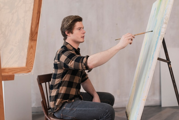 Vista laterale uomo artistico dipinto su tela