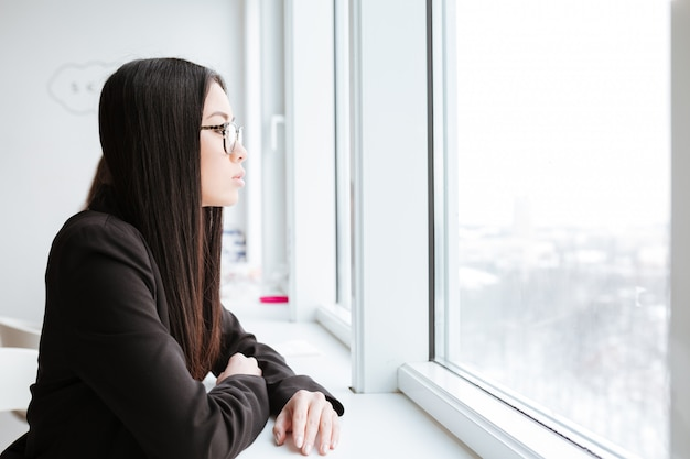 Side view of asian business woman looking at window
