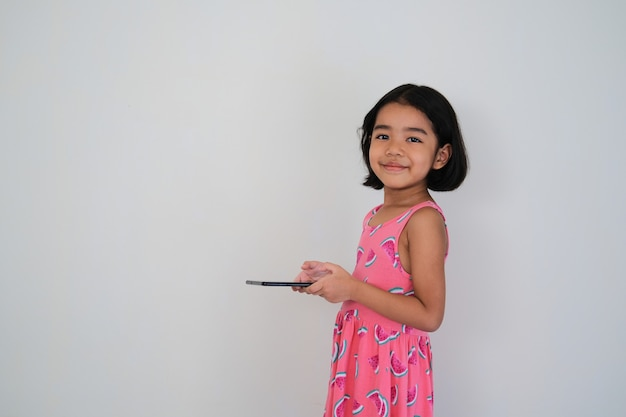Side view of asian little kid smiling when holding her mobile tablet