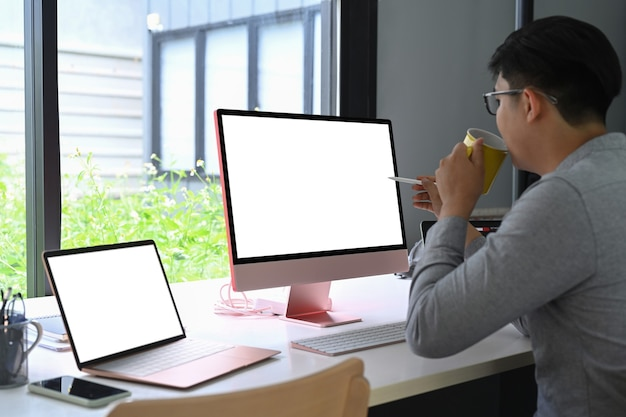 Side view asian man drinking coffee and working with modern devices.