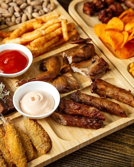 Side view of assorted beer snacks as grilled guails  french fries  pistachios and potato chips with sauces on a wooden board