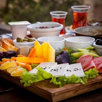 サイドビューのレストランの木製トレイにチーズ盛り合わせとティーグラスソーセージの朝食の盛り合わせ