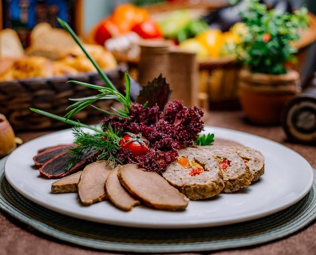 Вид сбоку ассорти из мясного ассорти из свинины с мясом, рулет, помидор басдирма и зелень на тарелке