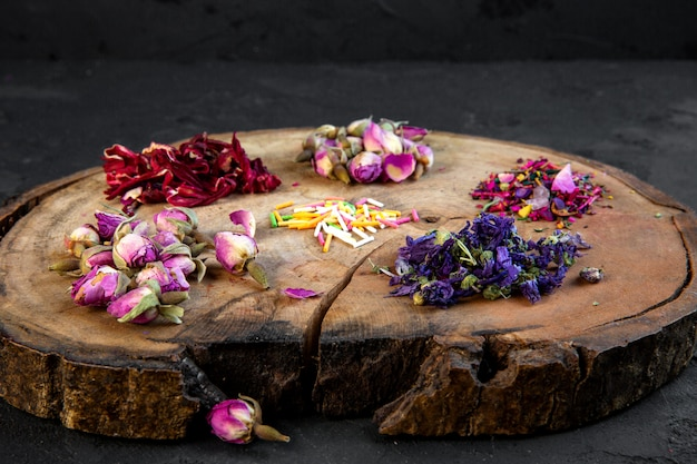 Side view of assortment of dry flower and rose tea on wooden board on black