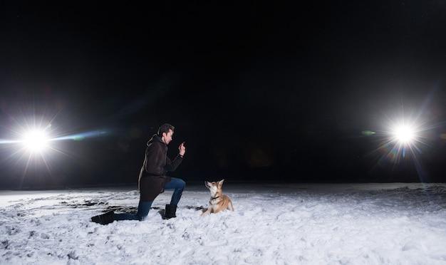 Вид сбоку на мужчину с двумя собаками смешанных пород на улице ночью зимой