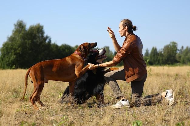 2匹の犬と若い白人男性の側面図