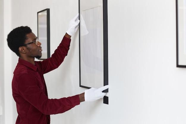 아트 갤러리 또는 전시회를 계획하는 동안 벽에 빈 프레임을 걸려 아프리카 계 미국인 남자의 측면보기,