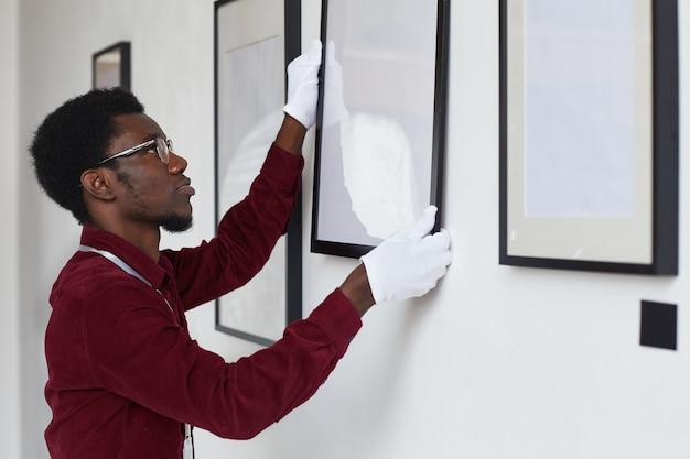 아트 갤러리 또는 전시회를 계획하는 동안 벽에 액자를 걸고있는 아프리카 계 미국인 남자의 측면보기,