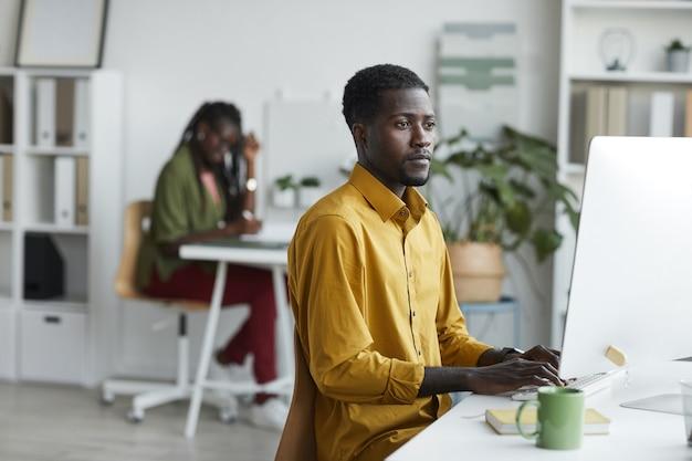 흰색 사무실 인테리어, 복사 공간에 책상에서 작업하는 동안 컴퓨터를 사용하는 현대 아프리카 계 미국인 남자의 측면보기