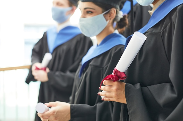 Вид сбоку на разнообразную группу молодых людей в выпускных платьях и масках, стоящих в ряду