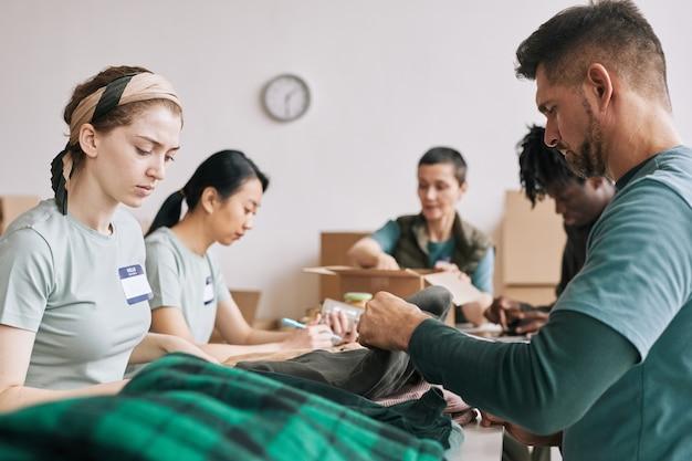 Вид сбоку на разнообразную команду волонтеров, занимающихся организацией еды и одежды во время мероприятия помощи и пожертвований, место для копирования