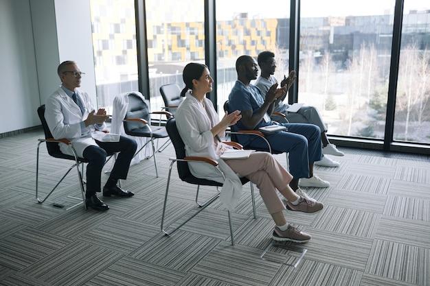 Вид сбоку на группу врачей, аплодирующих сидя на стульях во время медицинской конференции или семинара, копировальное пространство