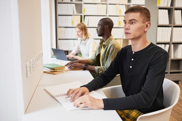 図書館で点字の本を読んでいる若い男と学生のグループの側面図