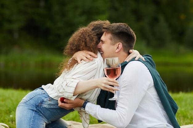 Вид сбоку на счастливую молодую женщину, обнимающую парня, принимая предложение руки и сердца во время романтического свидания на открытом воздухе