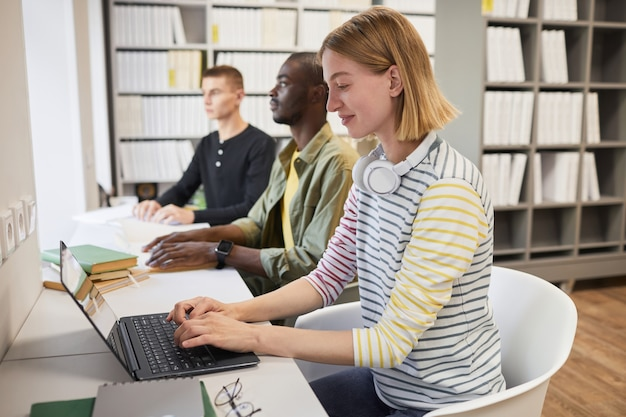 図書館で点字の本を読んでいる若い男と学生の包括的なグループでの側面図