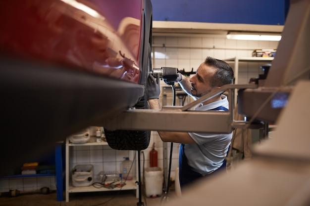 Вид сбоку на зрелый автомеханик, меняющий колеса красного роскошного автомобиля в авторемонтной мастерской, копировальное пространство