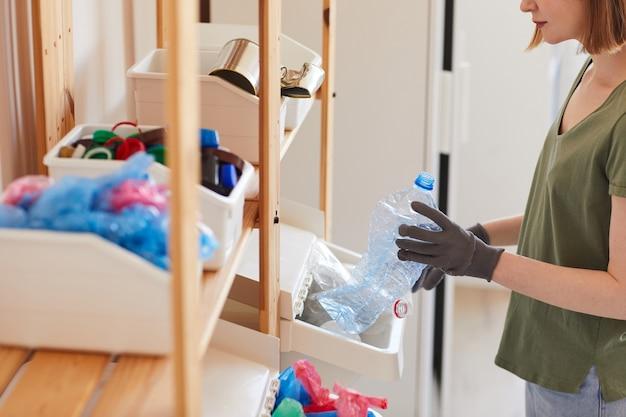 自宅で廃棄物を分別する現代の若い女性の側面図、保管とリサイクルの概念