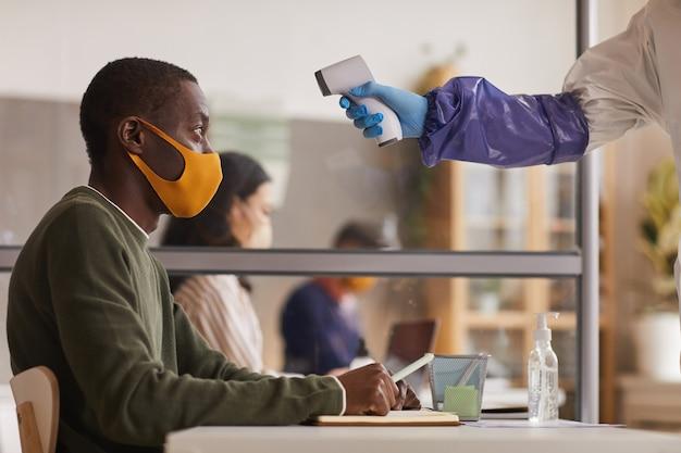 Вид сбоку на неузнаваемого медицинского работника, измеряющего температуру афроамериканца, работающего в офисе, копировальное пространство