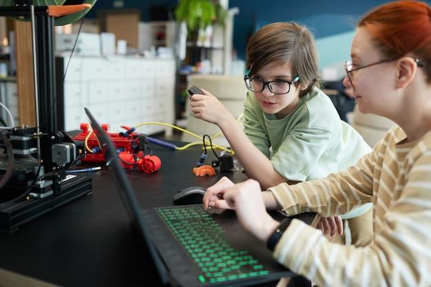 Вид сбоку на молодую учительницу, помогающую мальчику с помощью 3d-принтера во время урока робототехники и инженерии в школе