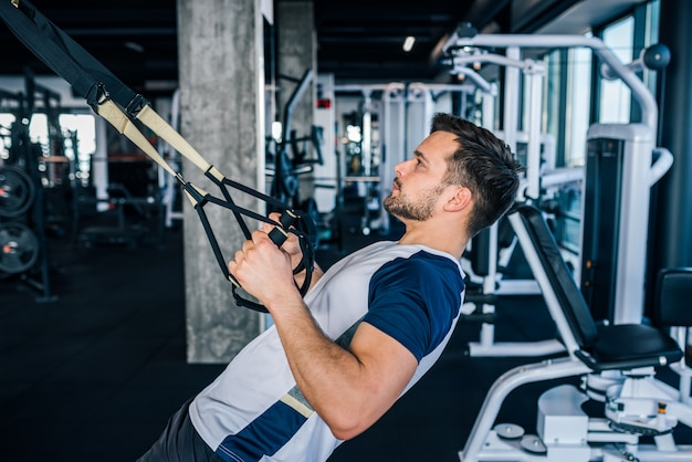 Side view of athlete doing exercises for back and arms with suspension straps.
