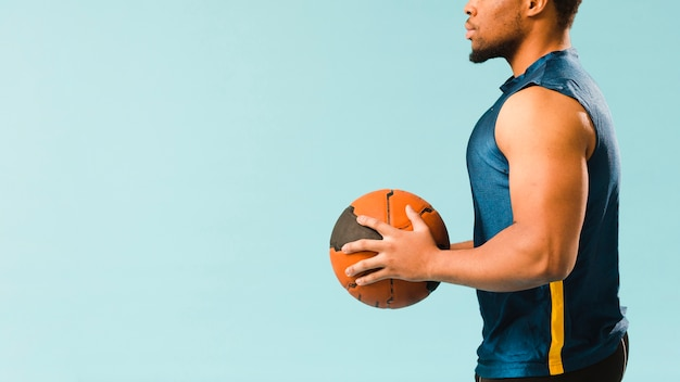 Side view of athlete holding basketball with copy space