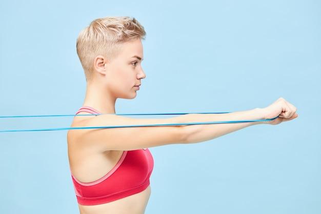 Vista laterale della giovane donna atletica sicura in cima rossa che si esercita alla parete blu usando la fascia di resistenza, tirandola per allenare i muscoli del braccio. concetto di forza, energia, determinazione e motivazione