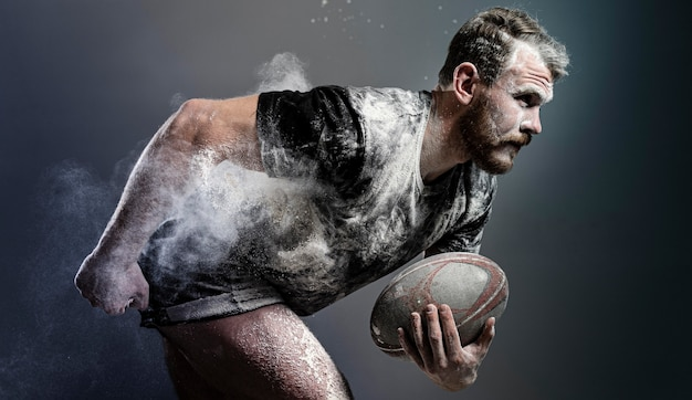 Side view of athletic male rugby player holding ball with dust