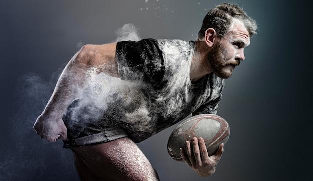 Vista laterale del giocatore di rugby maschile atletico che tiene palla con polvere