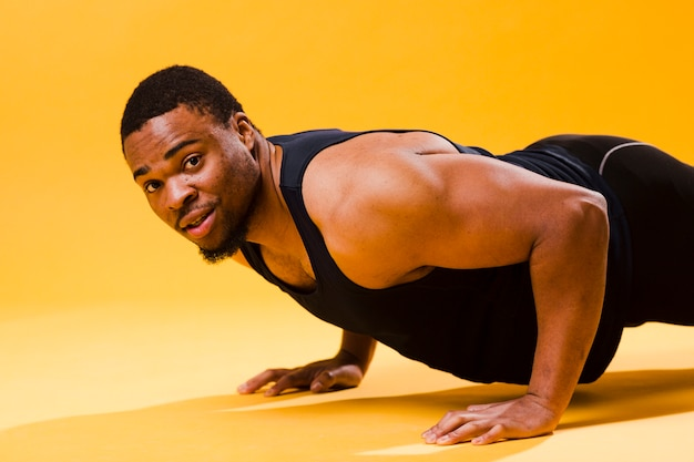 Side view of athletic man doing push up