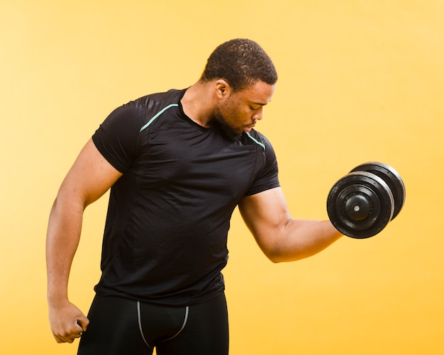 Side view of athletic man holding weights in gym outfit