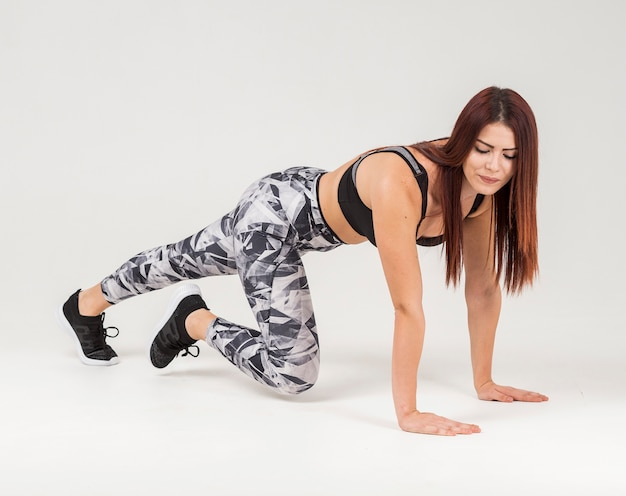 Side view of athletic woman doing plank