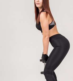 Side view of athletic woman doing squats while holding weight