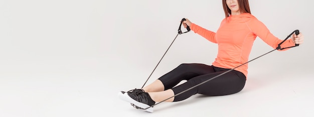 Side view of athletic woman exercising with resistance band