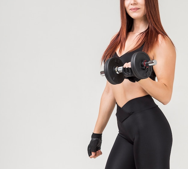Side view of athletic woman in gym attire exercising with weight