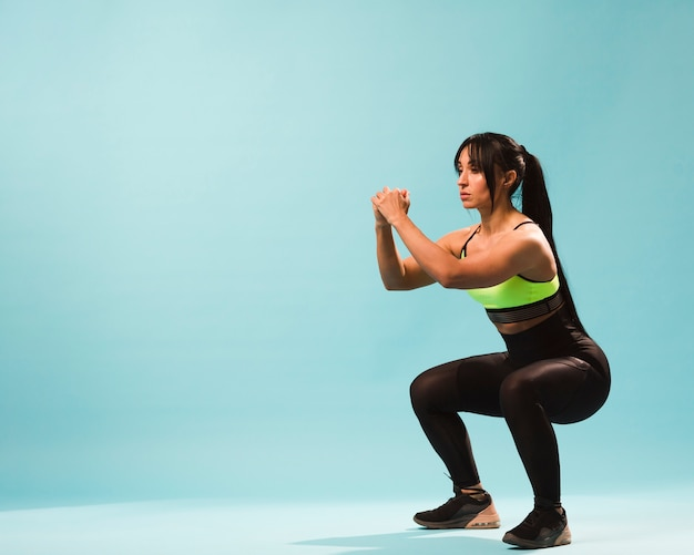 Side view of athletic woman in gym outfit doing squats with copy space