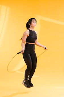 Side view of athletic woman in gym outfit jumping rope