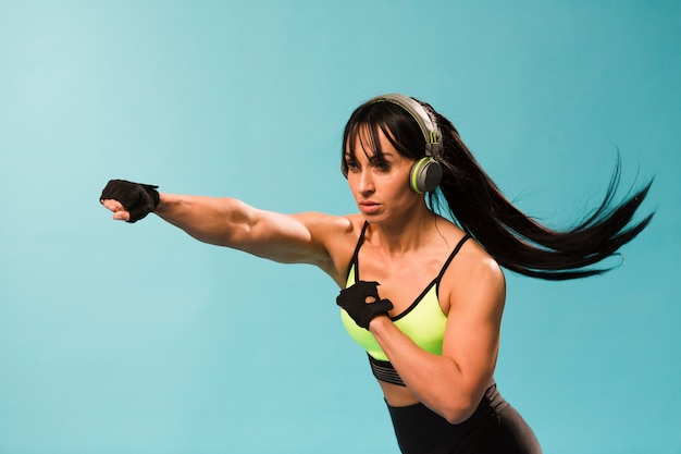Side view of athletic woman in gym outfit punching