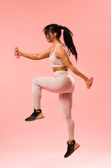 Side view of athletic woman jumping with weights