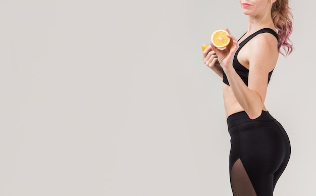 Side view of athletic woman posing with an orange in her hands