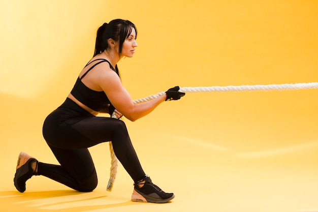 Side view of athletic woman pulling rope in gym outfit